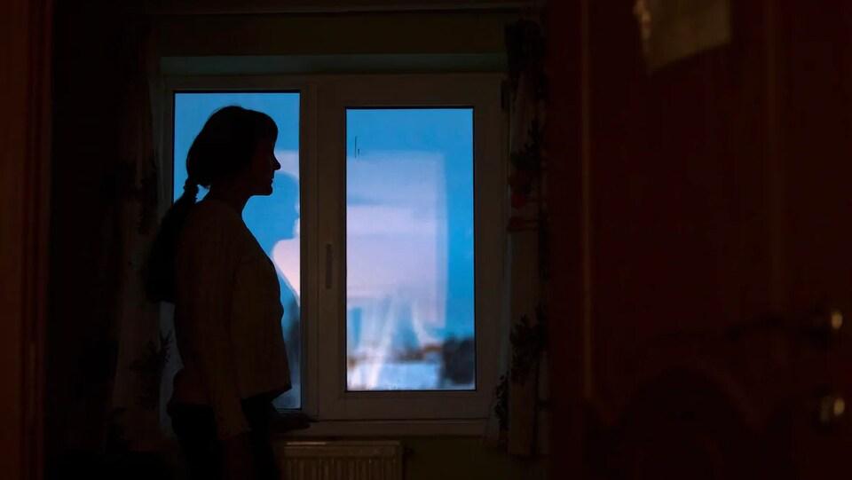 Vue sur une dame qui est devout à côté d'une fenêtre. Elle est dans le noir.