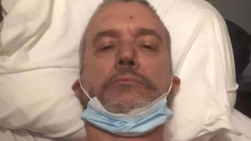 Un homme portant un masque chirurgical au cou est couché dans un lit d'hôpital.