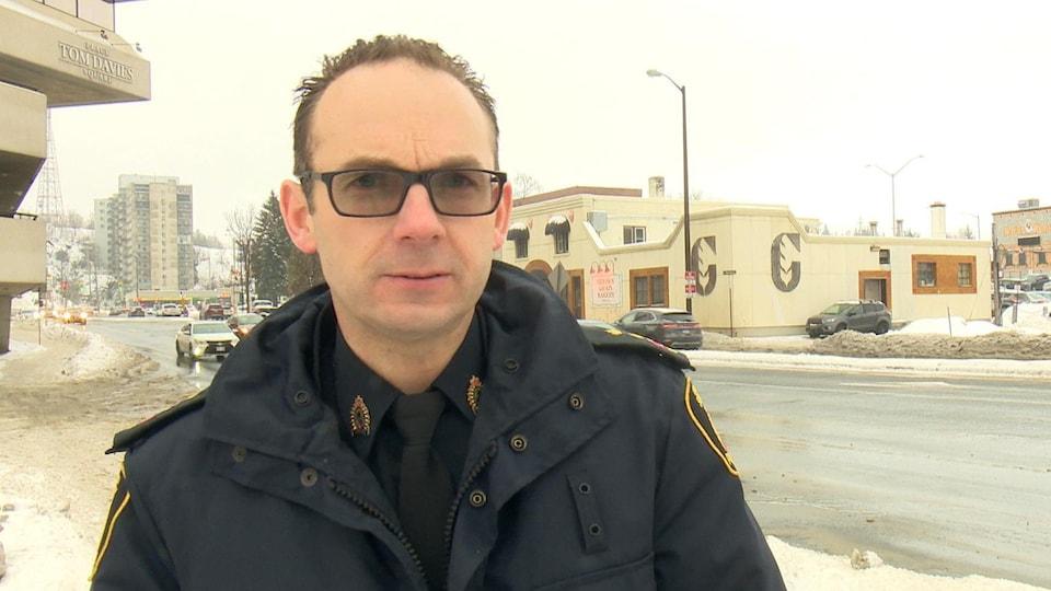 Un policier en uniforme se tient devant une route.