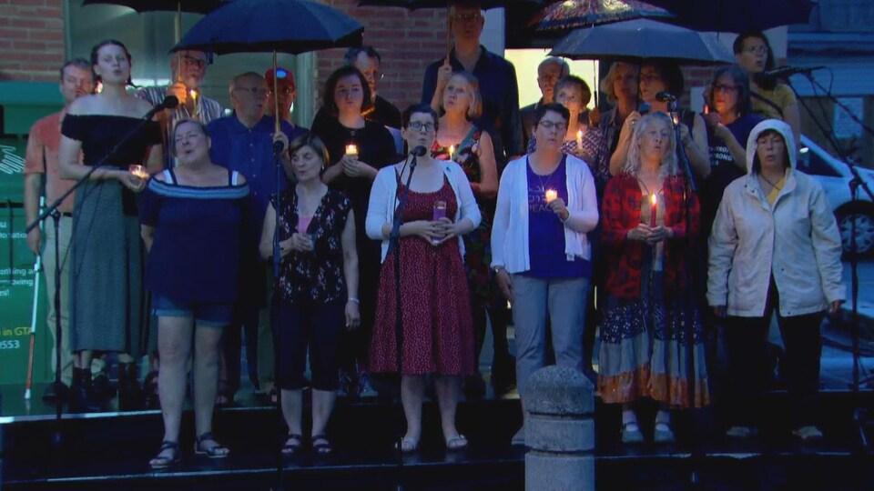 Une chorale qui chante sous la pluie à la tombée de la nuit.
