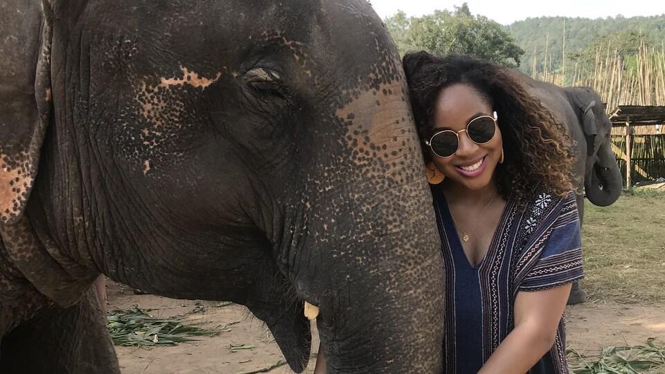 Une femme tient la trompe d'un éléphant.