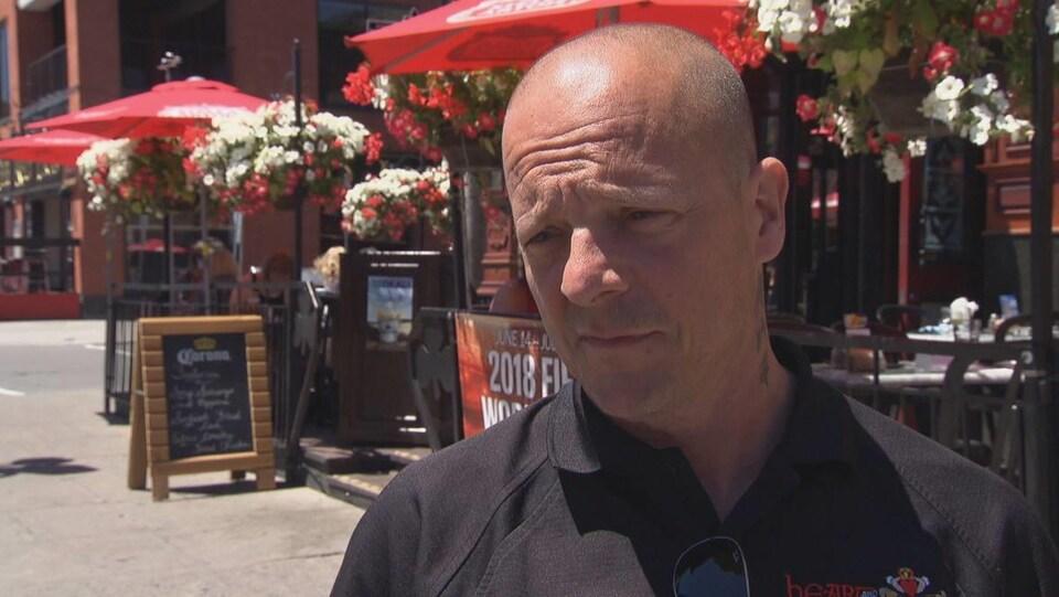 Un homme devant un bar du marché By à Ottawa en entrevue.