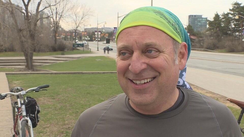 L'homme qui porte un bandana est interviewé le long d'un sentier cyclable sur le pont du Portage.