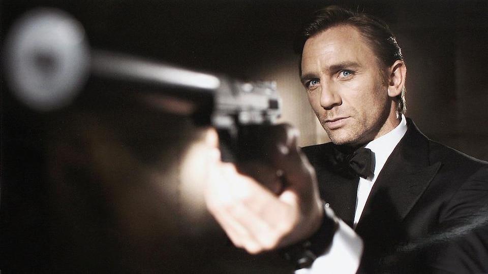 Daniel Craig porte un complet ainsi qu'un nœud papillon et tient une arme.
