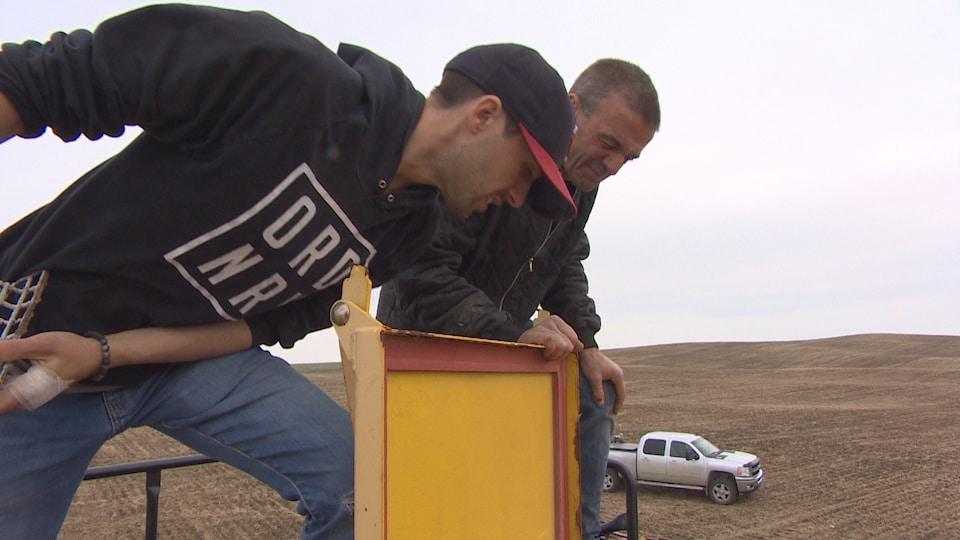 Daniel Charrière et son père Luc sont debout sur une semeuse, alors qu'un camion se trouve dans un champ à l'arrière-plan.