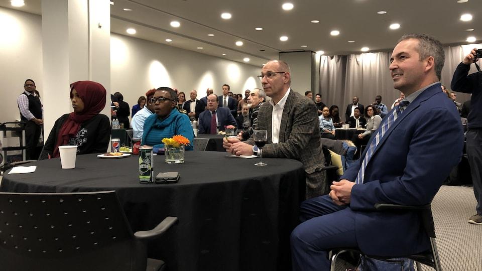 Daniel Giroux et d'autres gens sont attablés en écoutant une présentation.