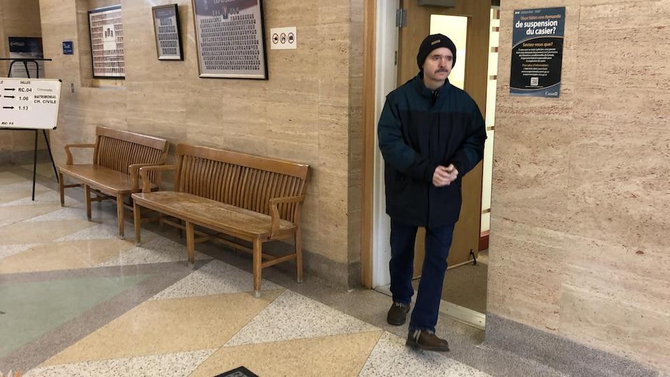 Daniel Laframboise marche dans le palais de justice.
