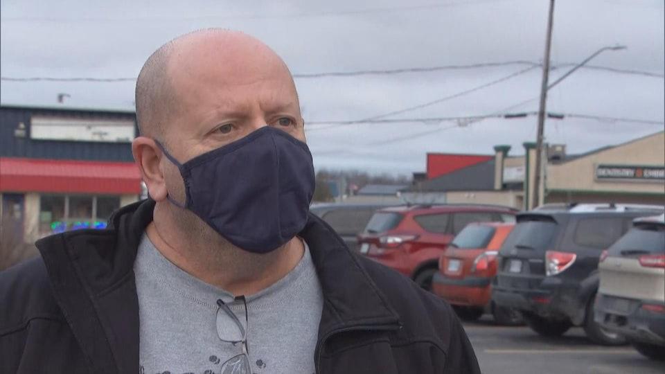 Un homme portant le masque accorde une entrevue à la caméra.