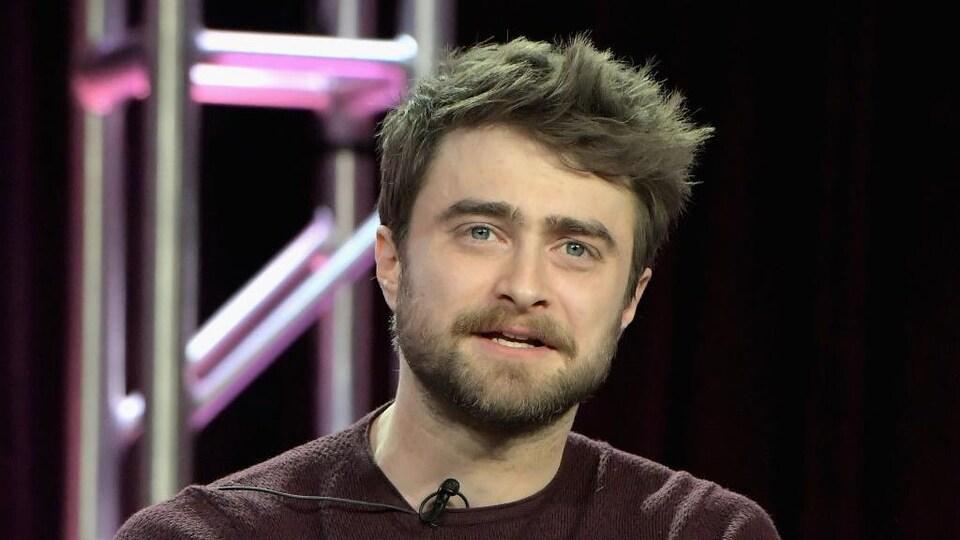 Daniel Radcliffe porte un chandail bordeaux.