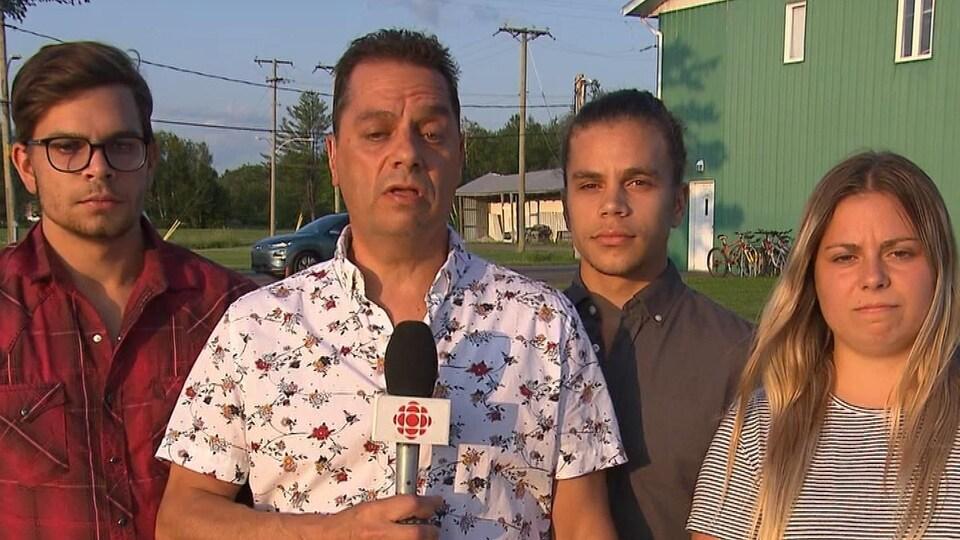 Daniel Roy parle à la caméra entouré de ses enfants.