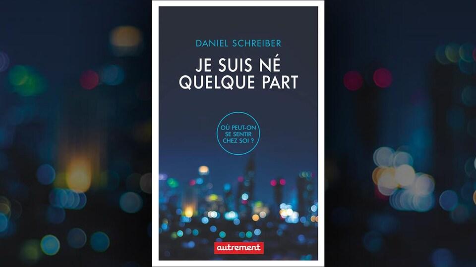 Sur la couverture du livre <i>Je suis né quelque part</i>, de Daniel Schreiber, on voit en arrière-plan, sous le titre et le sous-titre <i>Où peut-on se sentir chez soi?</i>, une photo floue de gratte-ciel illuminés.