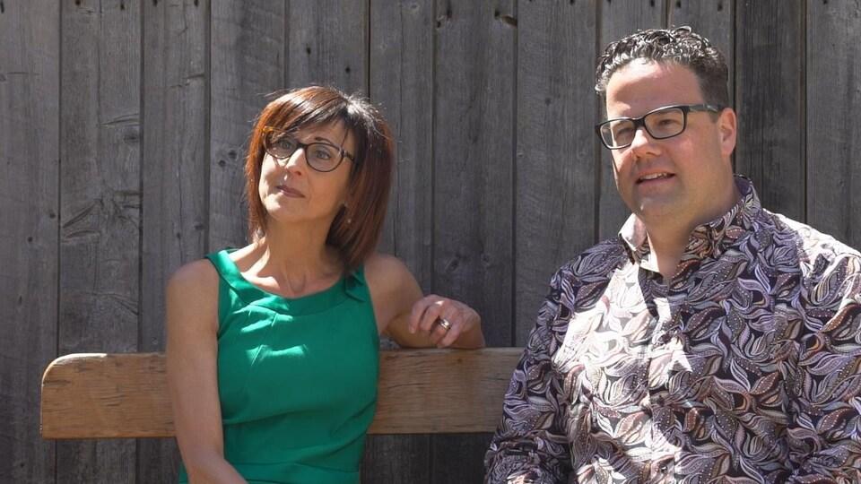 Un couple assis sur un banc, devant une façade de bois.