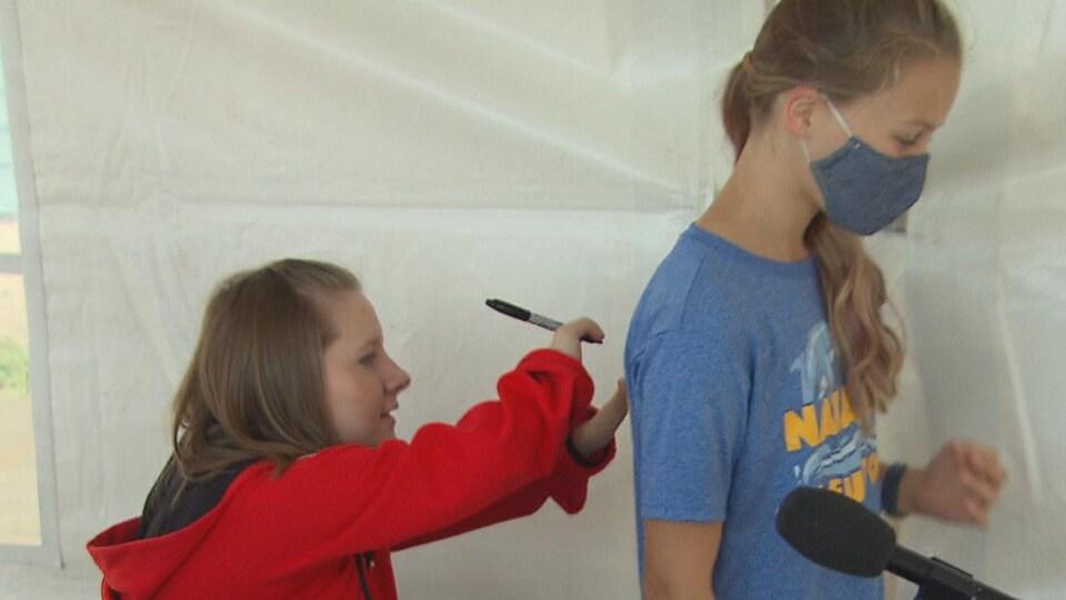 Une jeune femme assise, tenant un marqueur, signe un autographe sur le dos d'une adolescente debout devant elle.