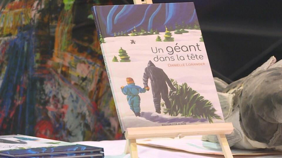 Le livre Un géant dans la tête, de l'autrice Danielle Loranger, se trouve sur un petit chevalet. La première de couverture présente la peinture d'un homme et d'un enfant de dos. L'homme tient la main de l'enfant de sa main gauche et tire un sapin dans la neige à l'aide de sa main droite.
