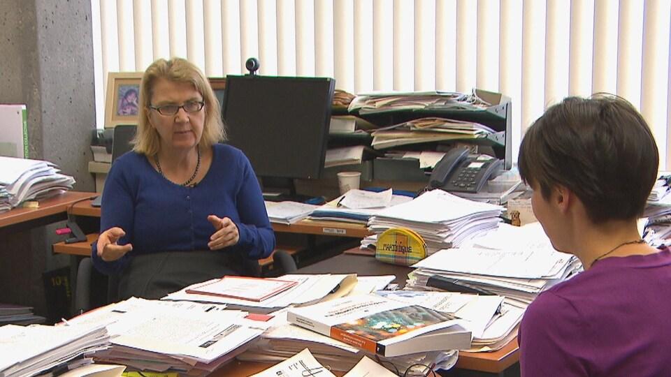 Danielle Maltais discute avec une journaliste, assise devant son ordinateur.