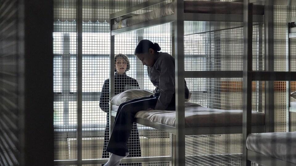 Le personnage de Waseese (joué par Brooklyn Letexier-Hart) est assise sur un lit, à l'intérieur une cage, surveillée par une gouvernante (Suzanne Cyr) dans le film Night Raiders.