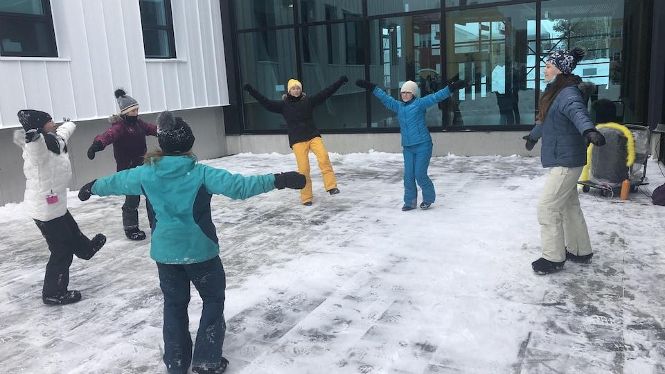 Des jeunes enfants dansent à l'extérieur en hiver