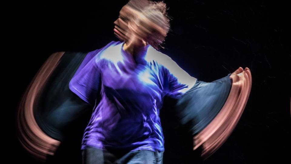 Une femme vêtue de mauve danse sur scène dans un mouvement répété dont on voit les lignes sur l'image.