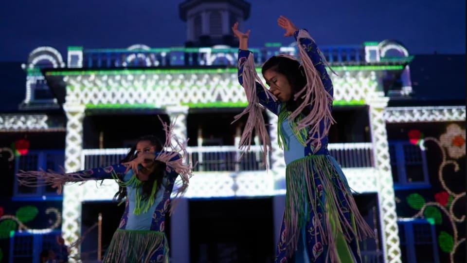 Deux femmes autochtones dansent devant un bâtiment illuminé.