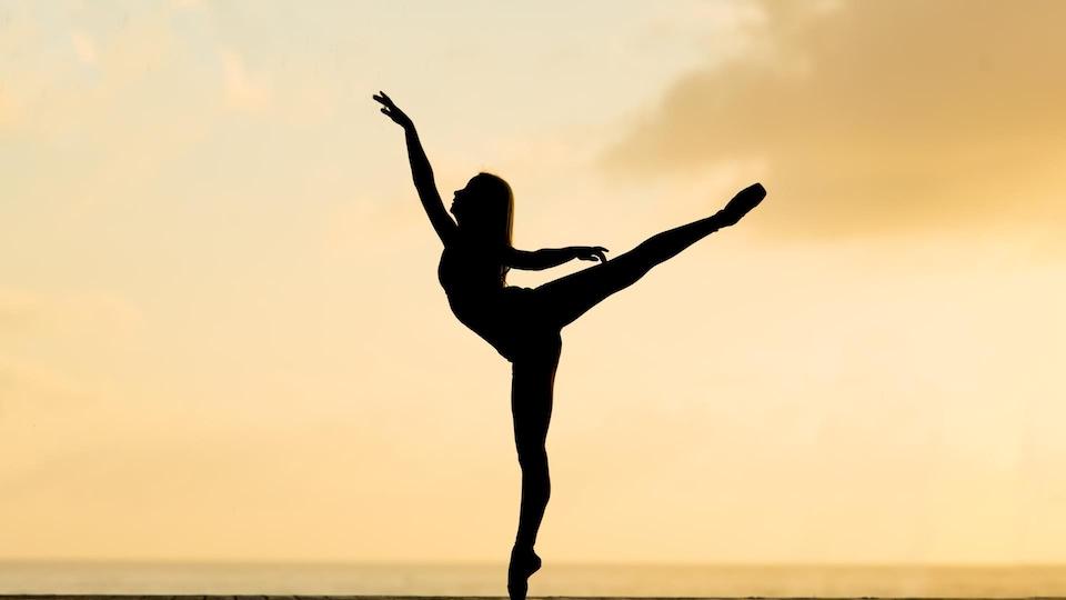 Une femme fait une arabesque.