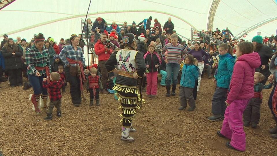 Des familles examinent les pas d'un danseur de pow-wow.