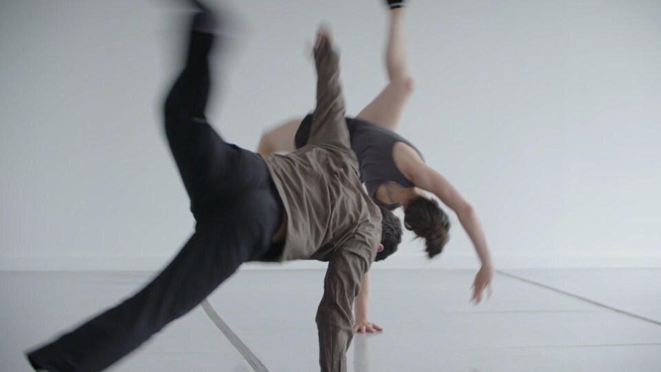 Deux danseurs effectuent une chorégraphie durant une répétition.