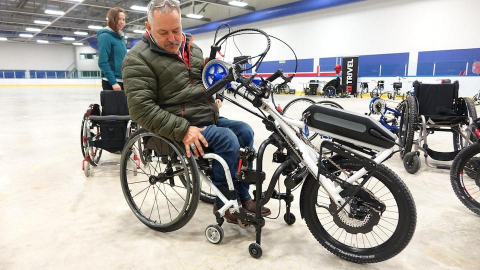 Dany St-Arnaud, propriétaire du Centre d'autonomie, fait la démonstration d'un vélo adapté hybride qui s'accroche directement à un fauteuil roulant
