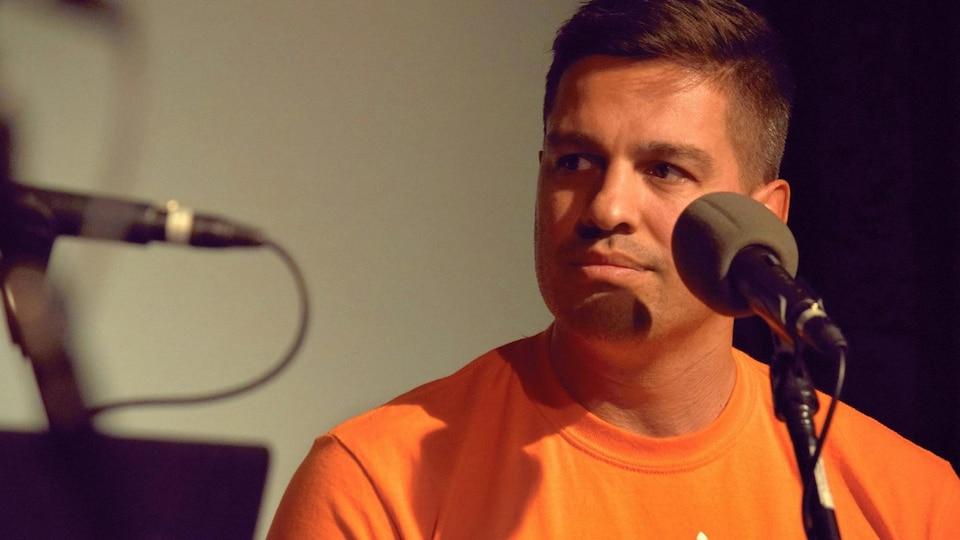Il est assis devant un micro lors d'une entrevue.