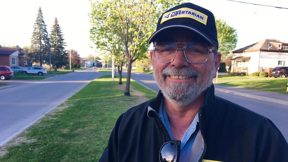 Un homme souriant et portant une casquette est debout sur un terre-plein.