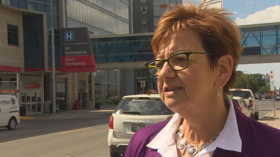 Plan moyen de Darlene Jackson donnant une entrevue dans la rue, avec en arrière-plan le Health Science Center de Winnipeg.