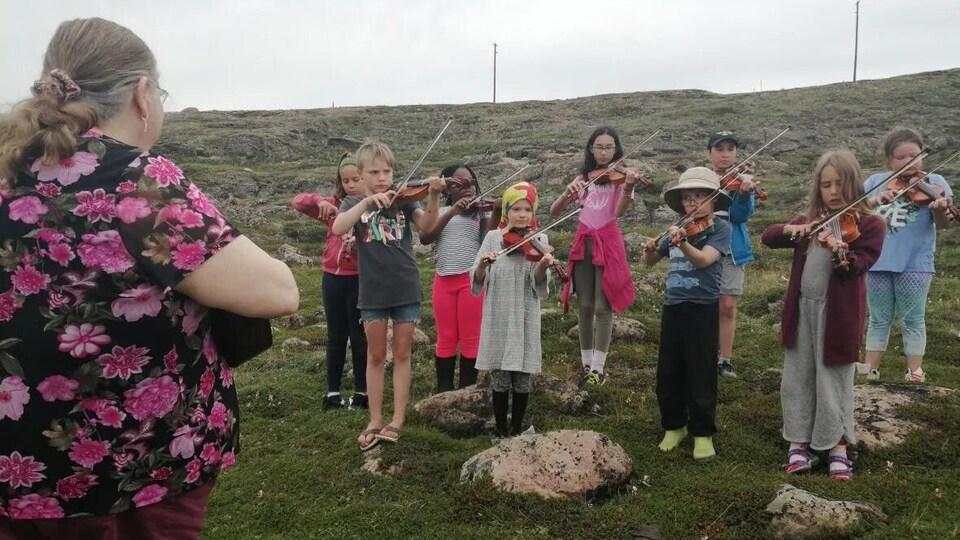 Des enfants jouent le violon devant Darlene.