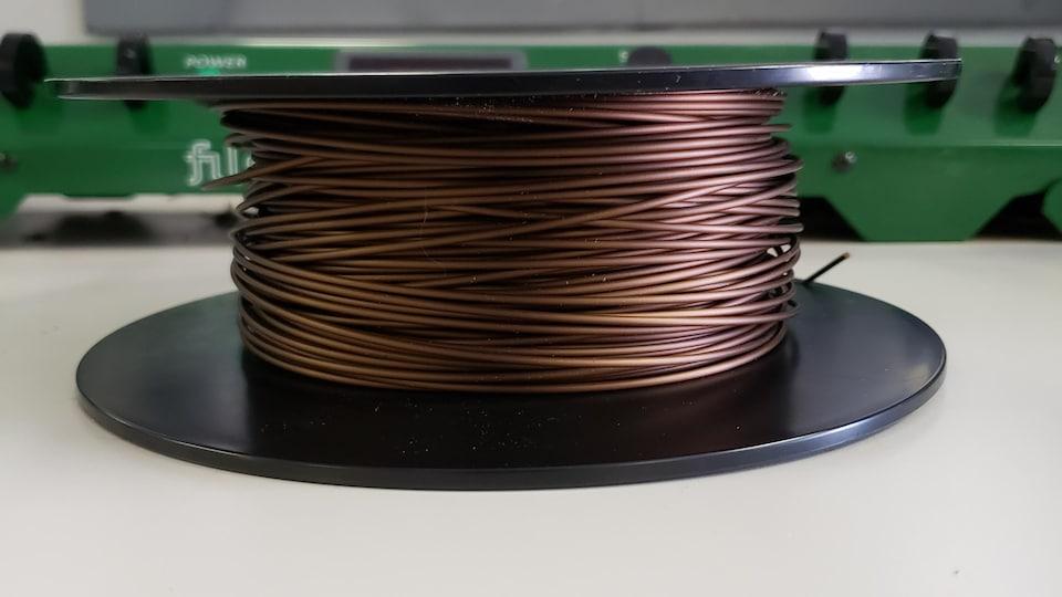 Une bobine repose sur une table.