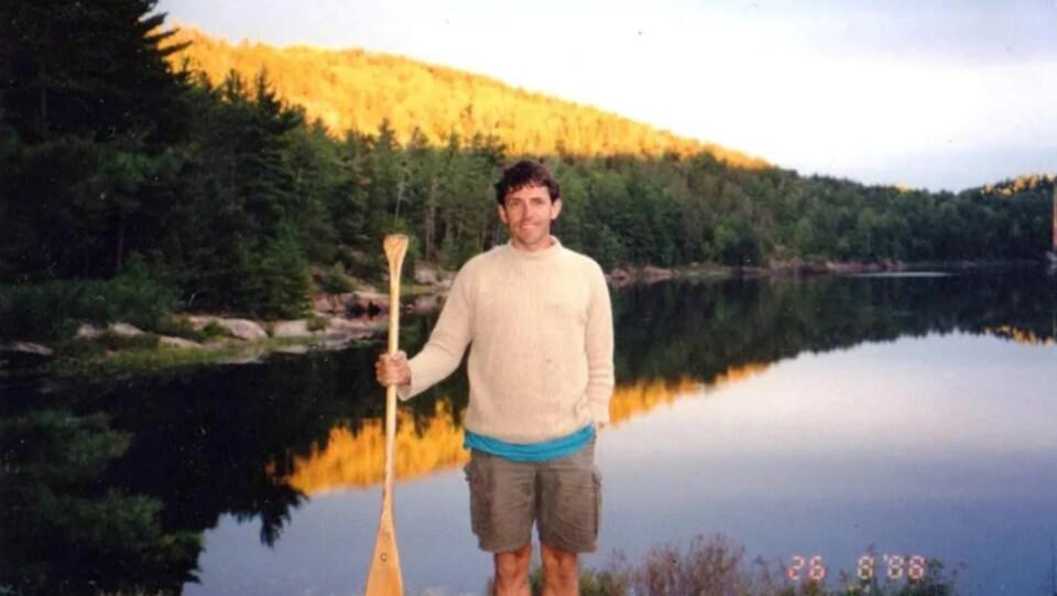 Darrell Johnson pose avec une pagaie devant un lac.