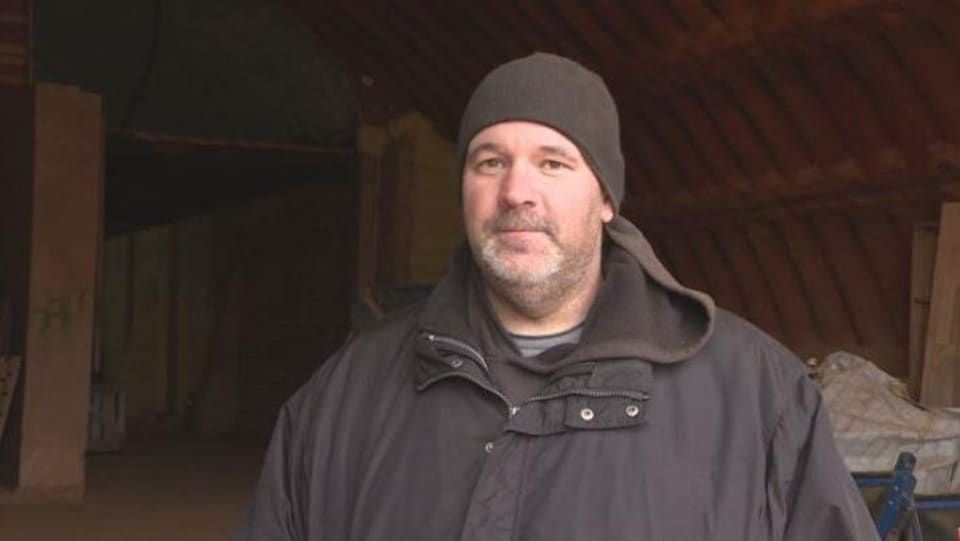 Un homme avec un manteau d'hiver et une tuque dans une grange.