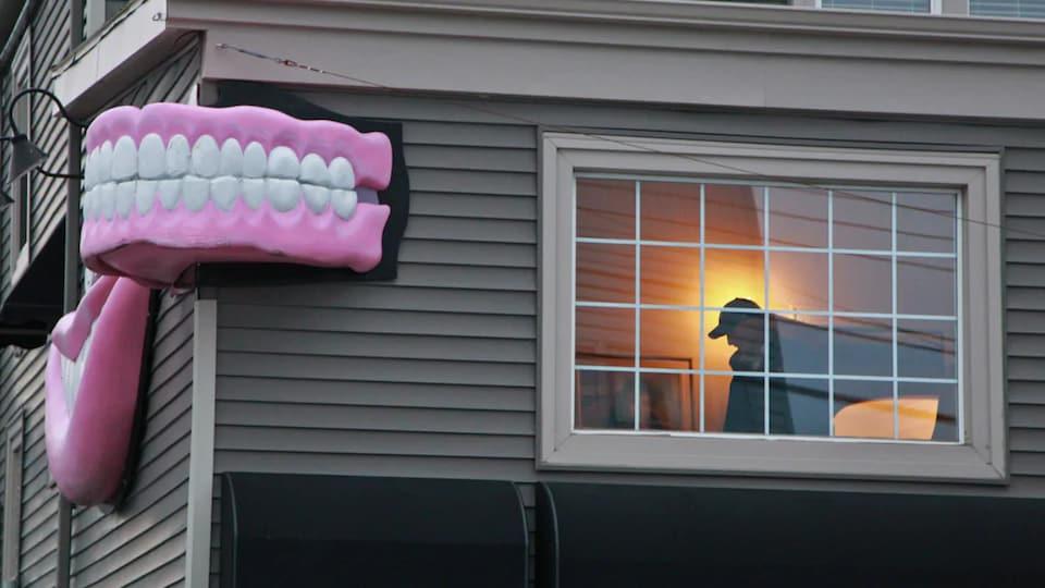 La silhouette d'un policier se dessine dans une fenêtre du bâtiment.