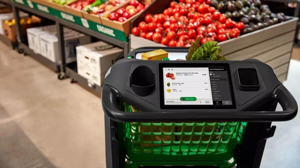 Un panier d'épicerie, vu comme s'il était devant nous, prêt à être utilisé. Il est équipé d'un gros écran tactile qui montre le prix des aliments.