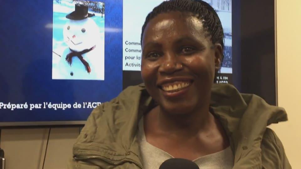 Gros plan sur le visage d'une femme qui répond aux questions du journaliste.