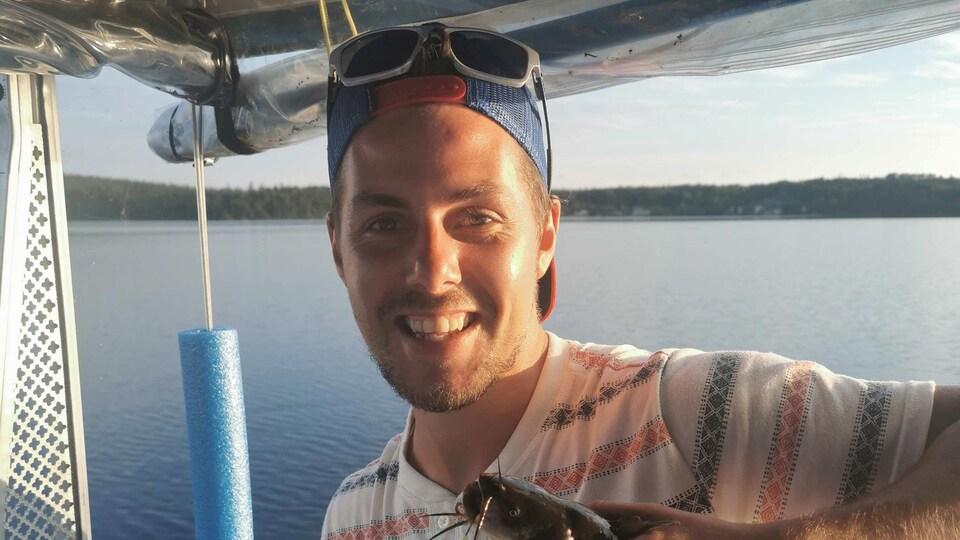 Dave Bellerose sur un bateau sourit en tenant un poisson dans sa main gauche.
