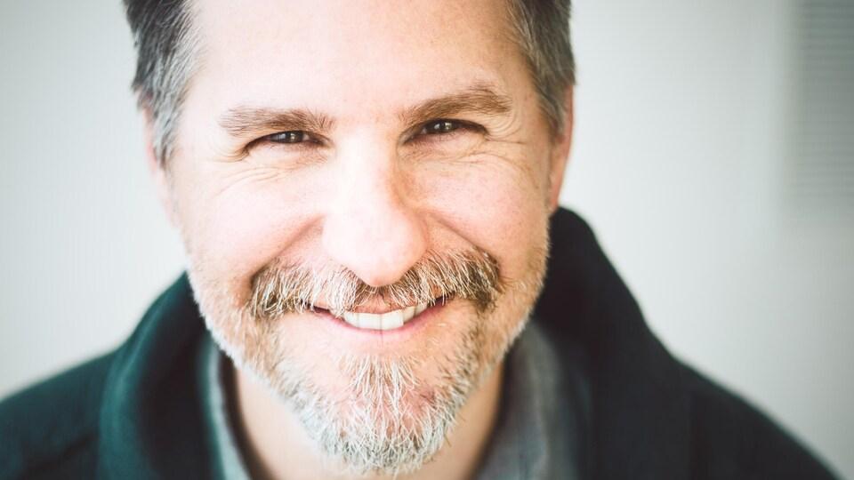 Portrait en couleur de Dave Jenniss. L'homme regarde l'objectif et sourit. Il porte un bouc.