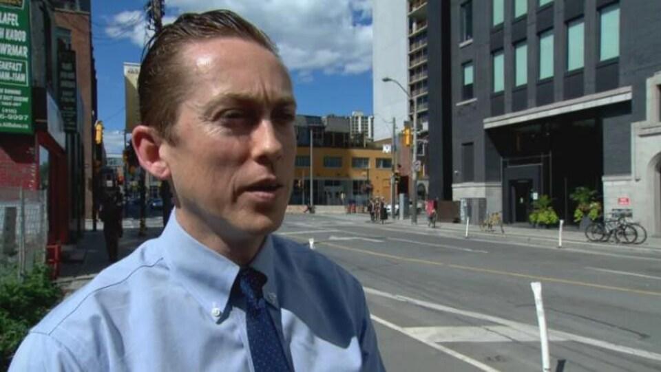 Dave Shellnutt porte une chemise bleu clair avec une cravate bleu marine, il est dans la rue. Il a le visage glabre, des cheveux gominés plaqués en arrière, blonds vénitiens.