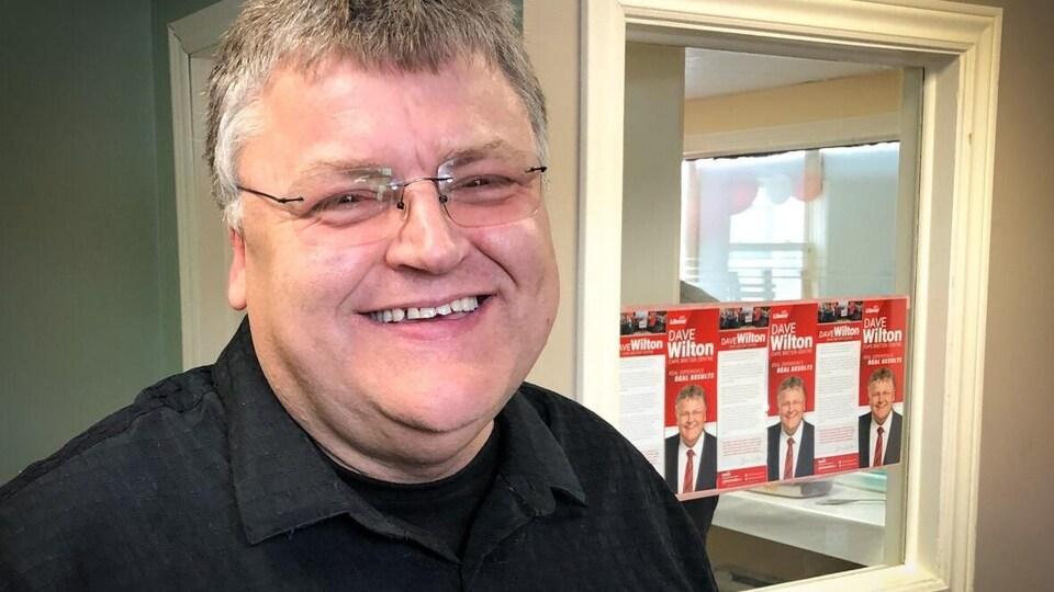 homme souriant devant pancartes électorales