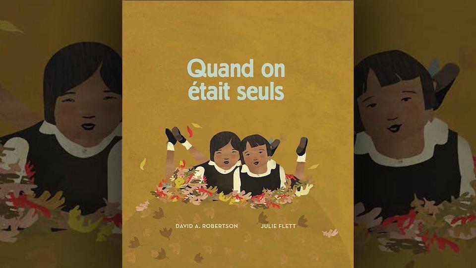 La couverture du livre Quand on était seuls, de David A. Robertson, illustré par Julie Flett. Illustration représentant deux fillettes à plat ventre sur des feuilles d'arbres, en uniforme, les pieds relevés.