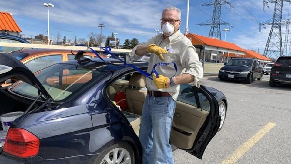 Un homme portant un masque défait des sangles pour attacher quelque chose sur le toit de sa voiture.