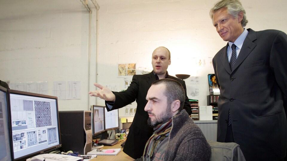 David Cage en train de pointer un écran d'ordinateur à Dominique de Villepin, pendant qu'un employé travaille devant eux.
