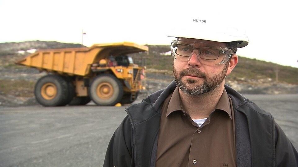 David Cataford avec un casque de construction. En arrière-plan, un camion lourd.