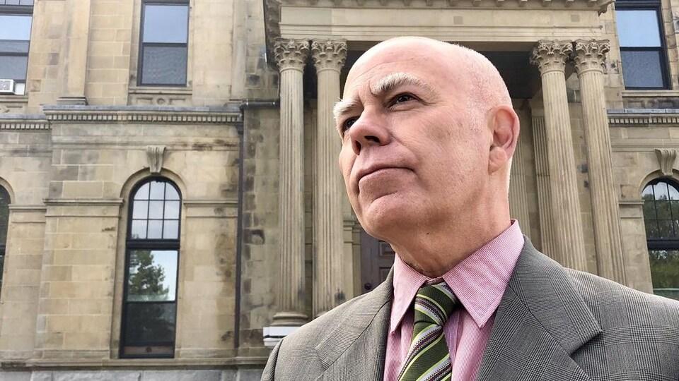 David Coon se tient fièrement devant l'Assemblée législative à Fredericton.