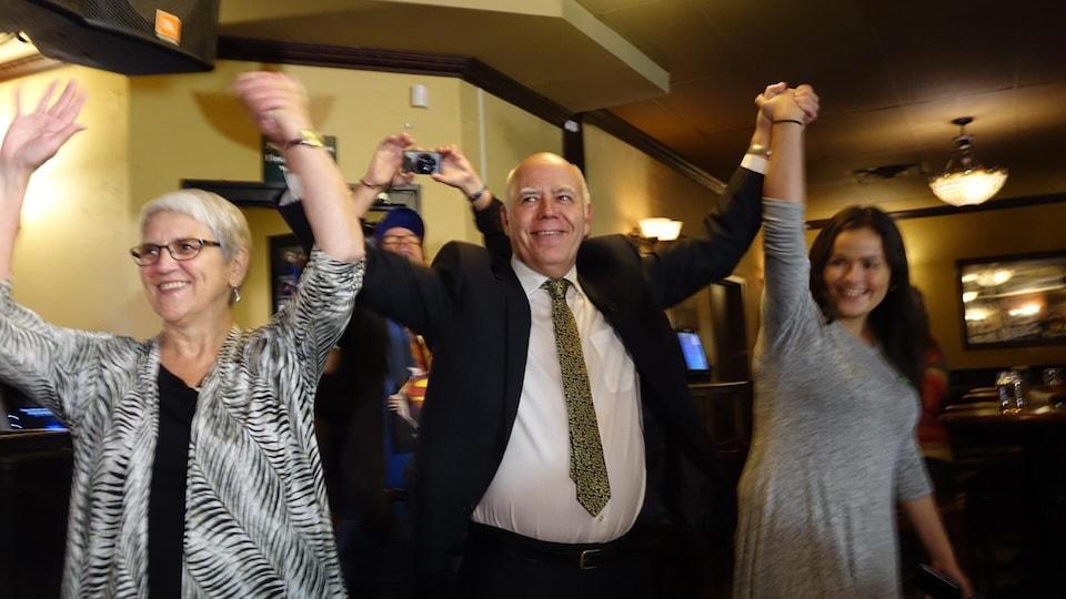 David Coon lève ses bras en l'air avec des militants.