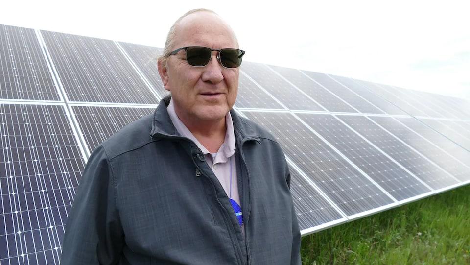 Un homme devant des panneaux solaires.