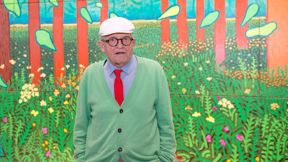 Portant un béret et des lunettes rondes, David Hockney a les mains dans ses poches et regarde l'objectif devant une de ses toiles.