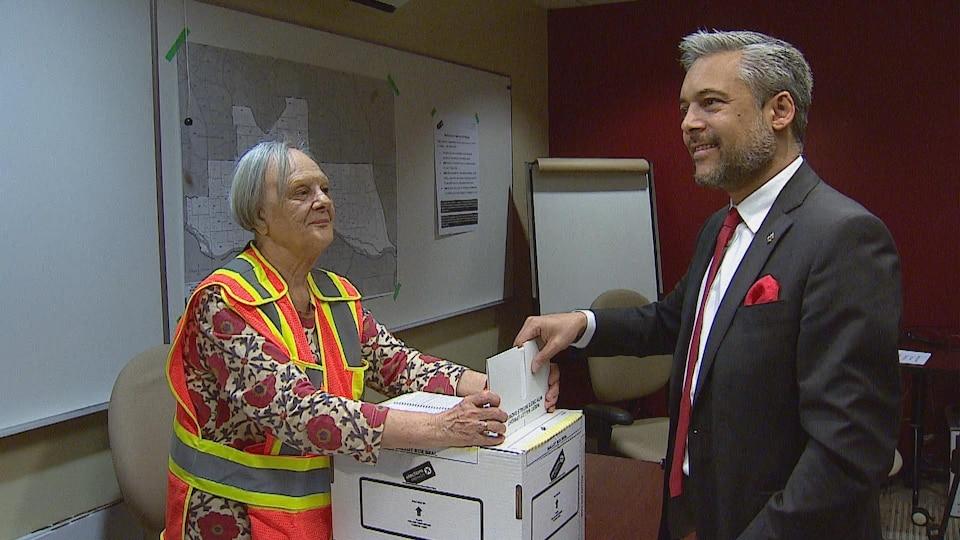 David Khan en train de déposer son bulletin de vote dans la boite. Une bénévole d'Élections Alberta lui sourit.